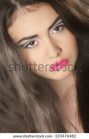 close up studio portrait of young beautiful woman with bright makeup