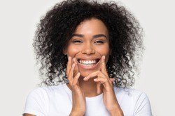 Close up studio portrait on grey background beautiful smiling african female holding dental floss cleaning teeth remove food between tooth preventing oral disease, concept of health care and hygiene