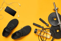 Close-up studio shot of a gym accessories on a yellow background. Top view, flat lay.
