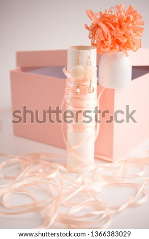 Close up studio shot of a pink gift box and a pair of handmade pearl earrings on white background, and this can be used as accessories elements or accessories background.