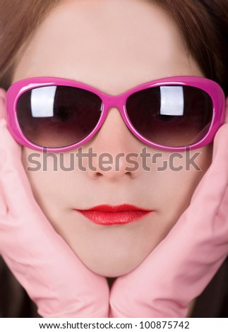 Close up studio shot of a young woman wearing pink sunglasses