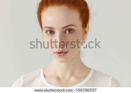 Close up studio shot of beautiful charming redhead European model with healthy freckled skin looking at camera with faint smile, posing indoors against blank wall background, wearing white t-shirt - Shutterstock ID 598780937