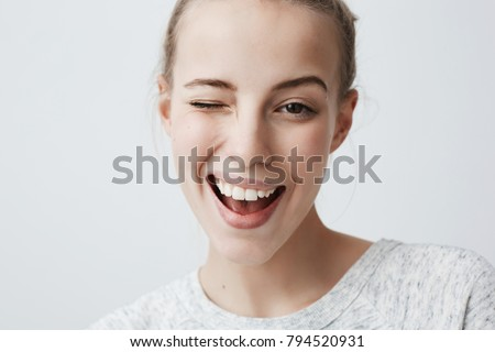 Close-up studio shot of positive coquettish young European woman with dark eyes, smiling happily, blinking at camera in a playful manner, flirting with you. Human facial expressions and emotions