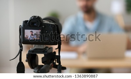 Close up successful man recording video, using digital camera in office or at home, successful freelancer, modern blogger, business coach making content, using professional equipment