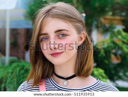 Close up summer fashion portrait of Beautiful Caucasian blond teenage girl in black choker. Beautiful young girl standing on street.Happy traveler.