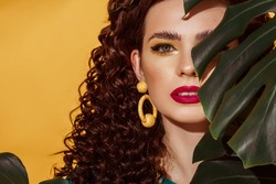 Close up summer fashion portrait of beautiful curly woman with fuchsia color lips, yellow eyes makeup, wearing big trendy earrings, posing on yellow background. Copy, empty space for text