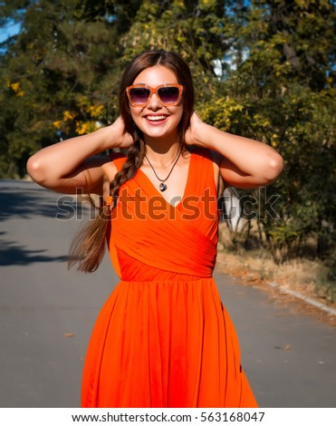 Close up summer fashion Portrait of young pretty woman posing at countryside, wearing stylish bright orange dress and mirrored sunglasses, warm pastel colors.