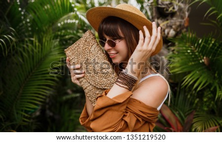 Close up summer fashionable  portrait of brunette woman in straw hat posing on tropical palm leaves background in Bali. Wearing stylish bohemian accessories.