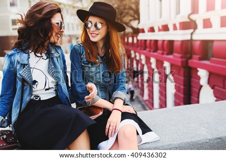 Close up  summer lifestyle portrait of two best friends laughing and talking  outdoor on the street in city center . Wearing stylish jeans jacket , dress, sunglasses. Enjoying time together.
