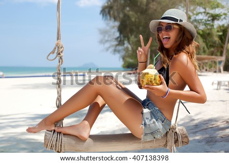 Close-up summer lifestyle tropical portrait of woman relaxing at hot sunny day over the white sand beach,Thailand,Similan islands,Hawaii USA.Drink fresh coconut and sunbathing,happy summer vacations