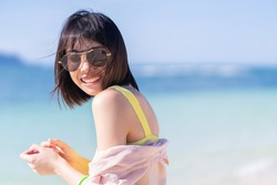 Close up summer portrait of young Asian woman in yellow bikini on tropical beach. Holliday summer concept