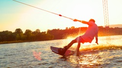 CLOSE UP, SUN FLARE: Unrecognizable athletic man wakesurfing on the lake at golden sunset. Young surfer dude having fun wakeboarding in the cable park on a beautiful summer morning. Fun water sport
