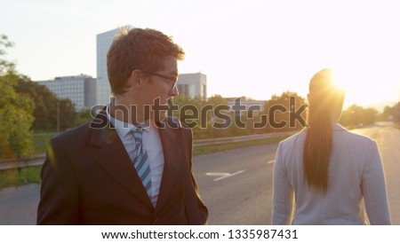 CLOSE UP SUN FLARE: Young Caucasian man looking at his phone stops and stares at gorgeous businesswoman walking to work at sunrise. Funny shot of businessman in awe of unrecognizable beautiful woman. ストックフォト ©