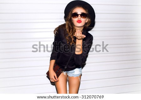 Stock Photo Close up sunny portrait of beautiful woman with fluffy brunette long hairs,smiling,having fun on the white wall,Sending kiss,wearing vintage sunglasses,Black leather outfit and hat,red lipstick smile