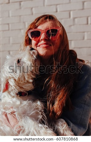 Close up sunny portrait of smiling blonde girl in sun glasses and happy west highland white terrier, beautiful friendship of dog and a human. Vertical pic #607810868