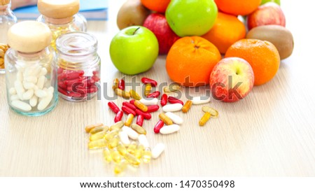 close up  supplement vitamins fish oil  ,vitamin E ,vitamin B capsules in glass bottles and pouring on the wooden floor including fresh fruits green and red apples, oranges and kiwi good for health