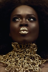 Close-up surreal portrait of majestic african american female model with gold glossy makeup. Fashion concept
