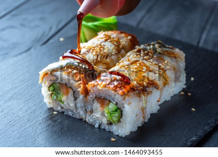 Close up sushi roll with cream cheese and eel. Sushi on stone dark plate on black wooden background with copy space. Japanese food. pour teriyaki sauce on sushi