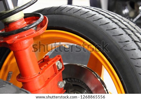 Close up suspension shock adsorber strut with spring,brake disc and alloy wheel of sport car #1268865556