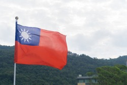 Close up Taiwan Flag with half mountain  and sky background