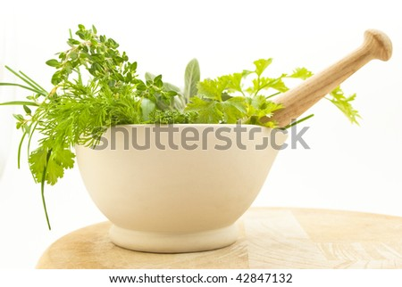 Close-up taken at eye level of pestle and mortar containing various culinary herbs, standing on a wooden chopping board.  White background.