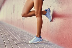 Close up  tans woman's legs in a white sneakers.