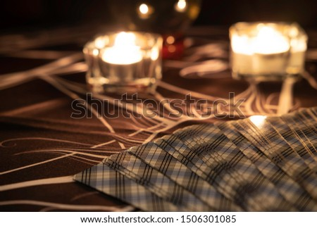 Close up tarot card spreads on a table with a crystal ball and burning candles in the background. Fortune teller reading  and  forecasting concept.Mystic and darkness background.