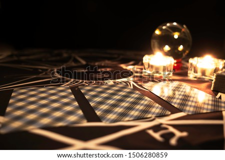 Close up tarot cards on  table with a crystal ball and burning candles in the background.Tarot reader or Fortune teller reading  tarot cards and forecasting concept.Mystic and darkness background.