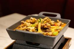 close up tasty Bullfrog Hotpot on restaurant table under light, Blur background. Popular Chinese cuisine