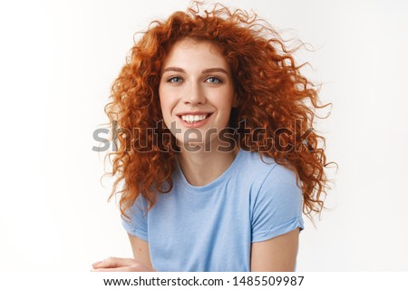 Close-up tender alluring redhead woman with curly hair that floats in air, smiling joyfully and coquettish gaze camera, enjoy summer ocean breeze, strands floating in air, stand white background