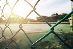 close up tennis fence. Green tennis fence with tennis court background. Outside sports background image.