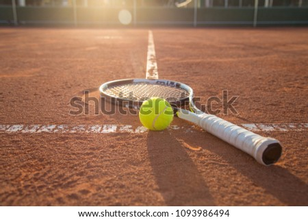 Close-up tennis racket and ball placed on court ground.