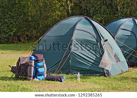 Close up tents and duffel bags on the green grass near the forest on a summer day - sports tourism, camping, scouting #1292385265