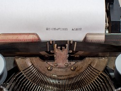 close-up text CORONAVIRUS ALERT. old vintage typewriter with a sheet of white paper