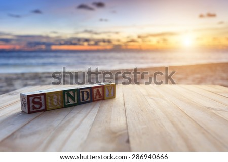 Close up text wood block on wood table at sunset or sunrise beach