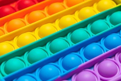 Close up texture of a Push Bubble Fidget Toy Pop It on yellow background.Trendy rainbow anti-stress sensory toy popit for popping bubbles