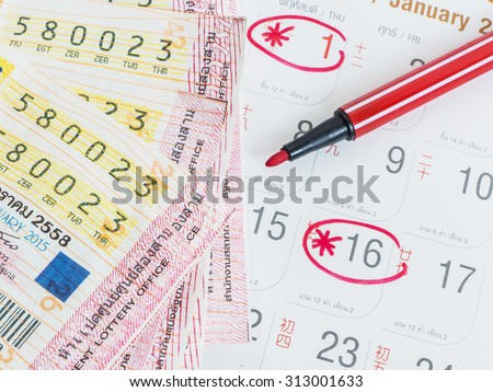 Close up Thai lottery tickets and Thai calendars with red marked of check out lottery date.