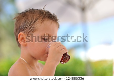 Close up the boy drinks in a heat from a glass juice