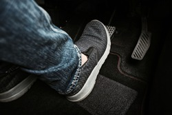 Close up the foot pressing brake pedal of a car. Driver stopping the car.