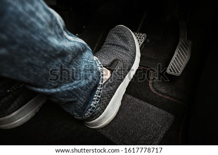 Close up the foot pressing brake pedal of a car. Driver stopping the car. Сток-фото ©