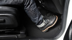 Close up the foot pressing foot pedal of a car to drive. Accelerator and brake pedal in a car. Driver driving the car by pushing accelerator and break pedals of the car. inside vehicle. control pedal.