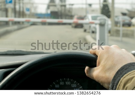 Close up, the hand of the driver of the car on the background of a closed barrier to enter the Parking lot of the protected object #1382654276