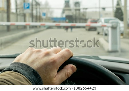 Close up, the hand of the driver of the car on the background of a closed barrier to enter the Parking lot of the protected object #1382654423