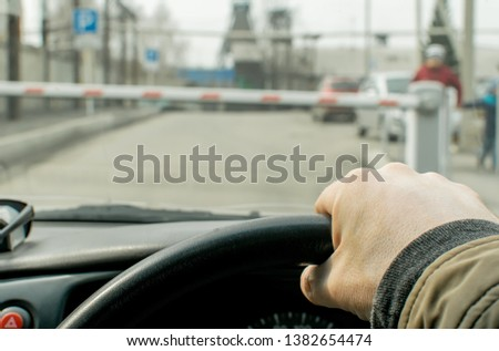 Close up, the hand of the driver of the car on the background of a closed barrier to enter the Parking lot of the protected object #1382654474