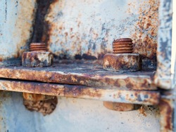 Close up the old metal bolts with rust. Bolts and bolts fasten the steel plates to rust, brown and are corrosive. On the old gray metal pipe background