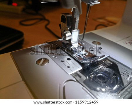Close up the sewing machine and item of clothing. #1159912459
