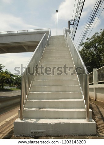 Close up the stairs of the overpass or footbridge. The side has a stainless steel rail on both sides to prevent the danger of people while using the flyover. The background is blue sky. #1203143200