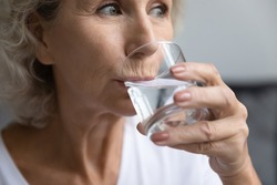 Close up thirsty beautiful middle aged woman drinking fresh pure mineral water, satisfied senior mature female holding glass, natural beauty and healthcare, healthy lifestyle, good daily habit