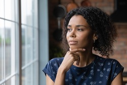 Close up thoughtful African American woman looking out window to aside, touching chin, dreamy young female lost in thoughts, planning, visualizing future, businesswoman thinking, making decision
