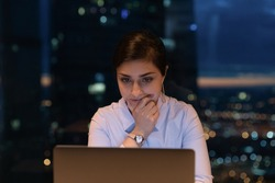 Close up thoughtful Indian businesswoman using laptop at late hours, finishing, working on project at night, touching chin, looking at computer screen, pondering, solving problem, deadline concept